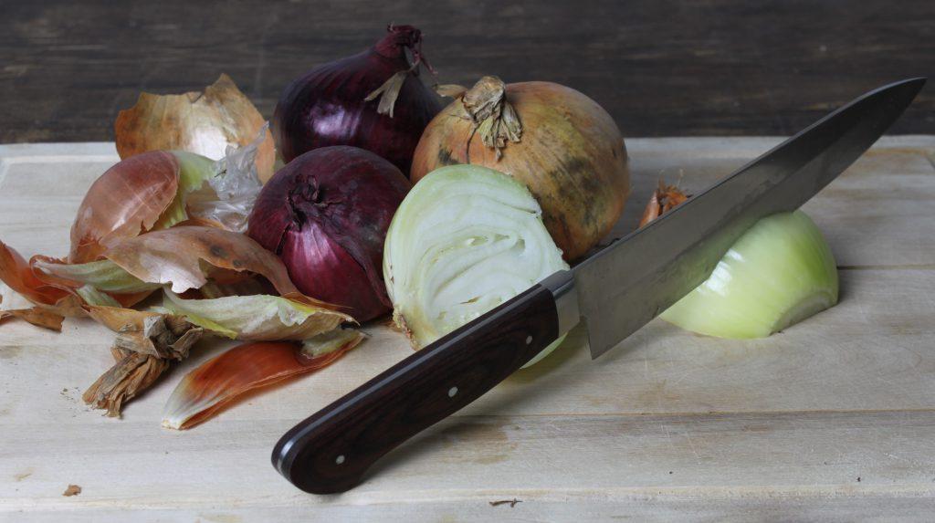 Für die vegane Soljanka die Zwiebelhälften in dünne Scheiben schneiden