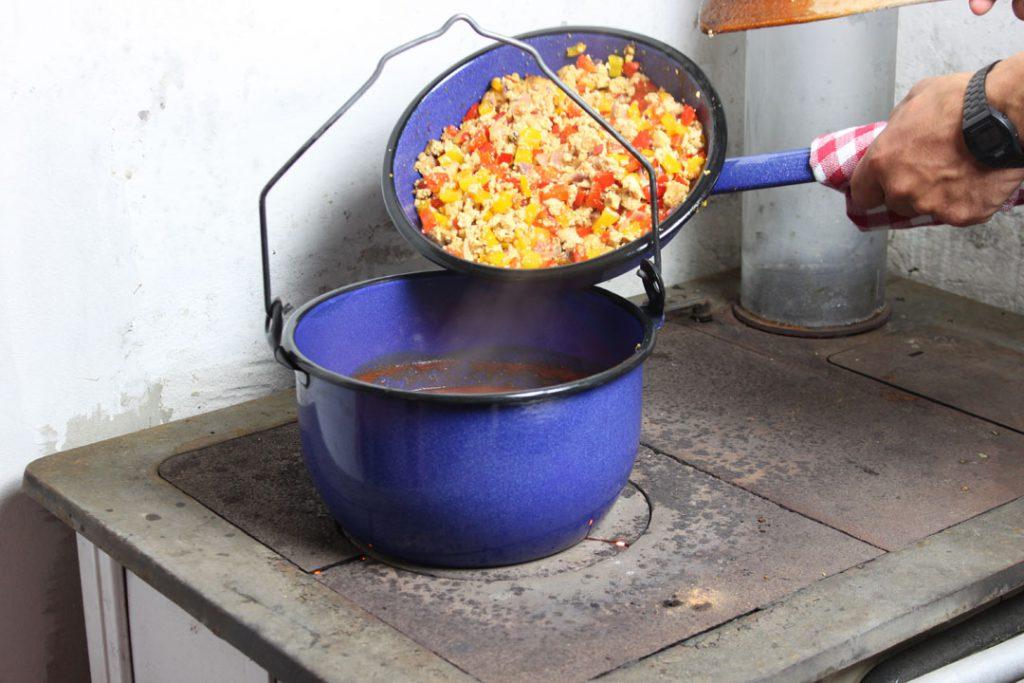 Die angebratenen Zutaten zum Chili-Sud geben