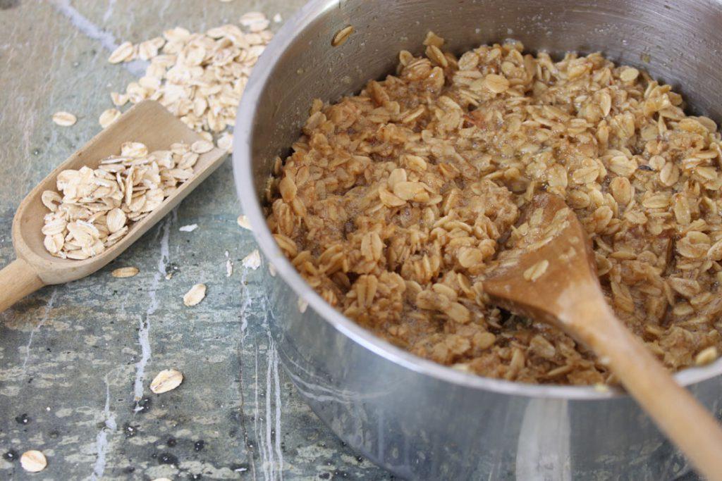 Für vegane Energieriegel die Margarine schmelzen und zusammen mit den Haferflocken und dem Zucker kurz kochen