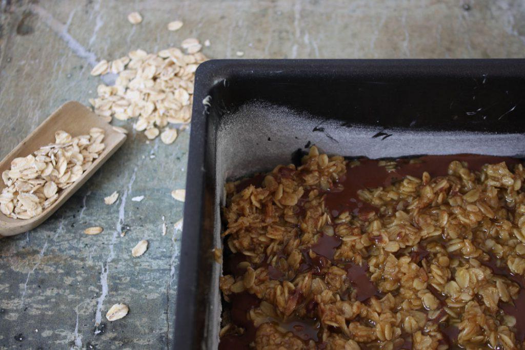 Die Schokolade verstreichen und die restliche Haferflockenmischung darauf verteilen