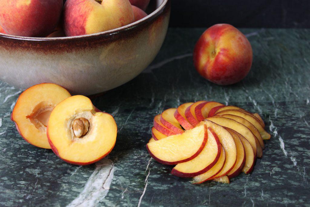Die Pfirsiche in dünne Scheiben schneiden