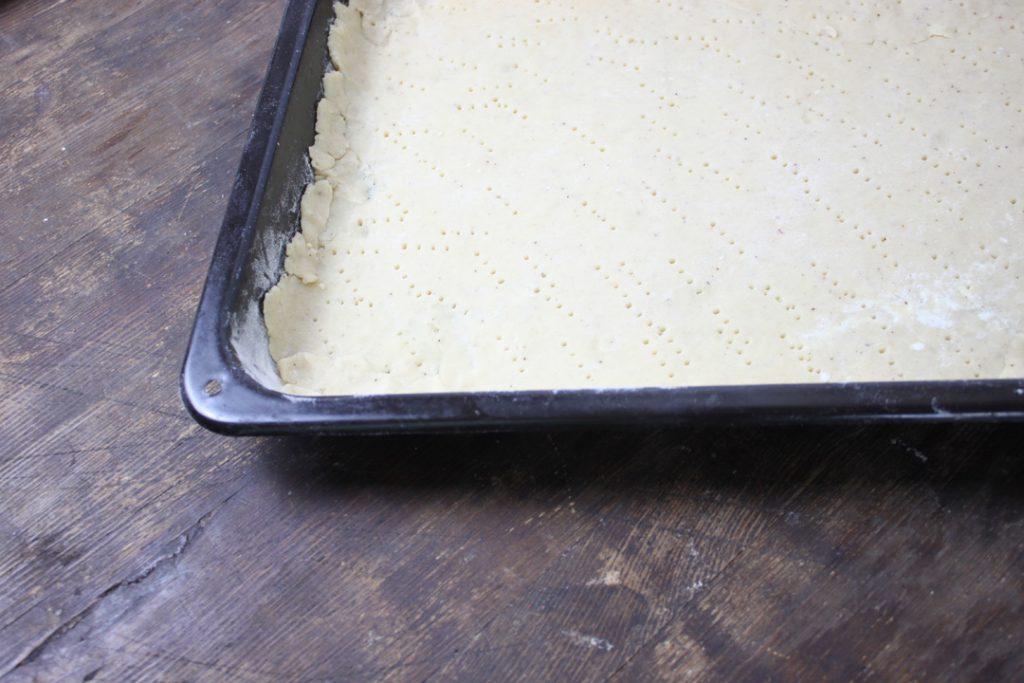 Den Teig ausrollen, auf ein gefettetes Blech geben und mehrmals mit einer Gabel einstechen