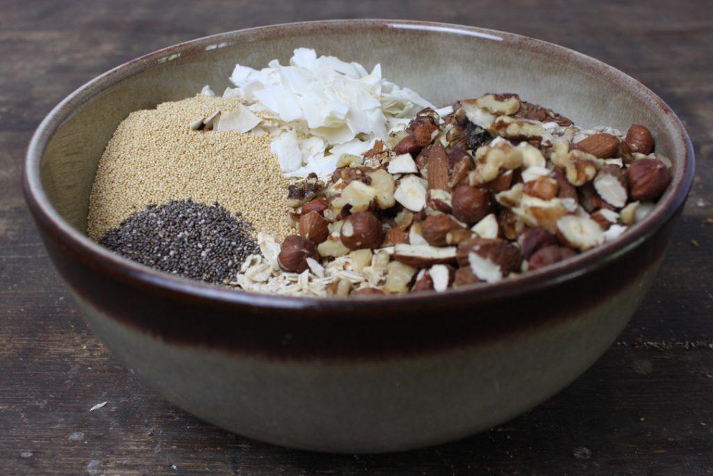 Flocken und Nüsse in einer Schüssel für Euer selbstgemachtes Müsli vermengen