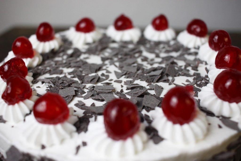 Die Torte mit Tuffs und Kirschen verzieren