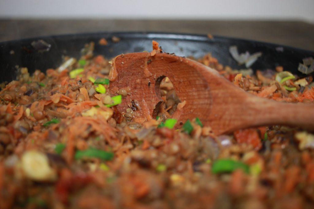 Die getrockneten Tomaten und die geriebene Möhre in die Pfanne geben