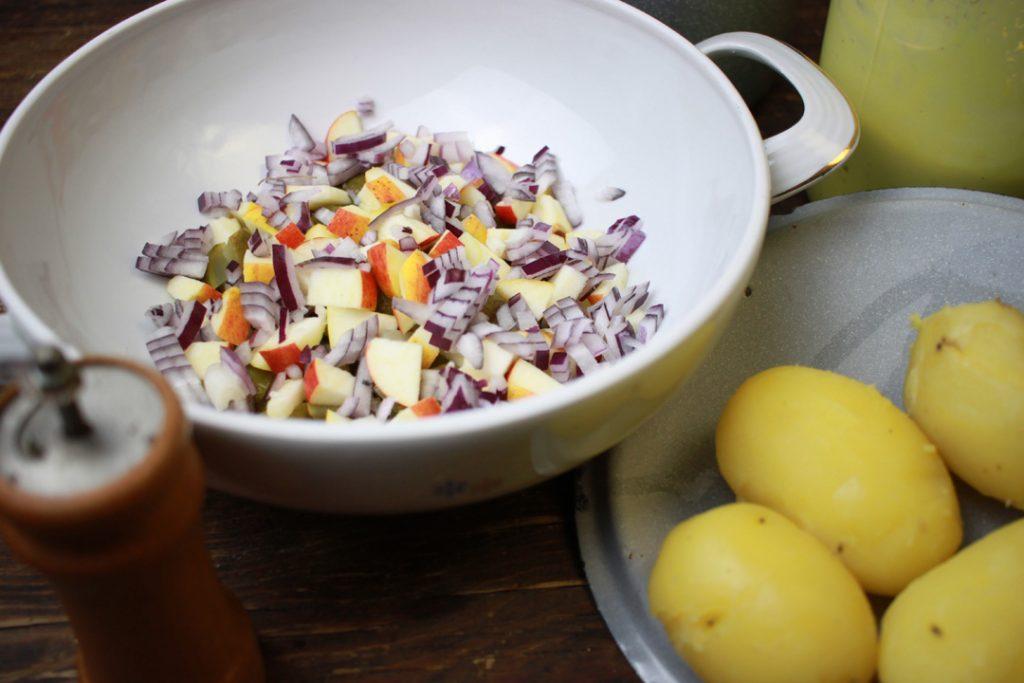Veganer Kartoffelsalat punktet mit frischen Zutaten wie Zwiebel, Apfel und Gewürzgurken