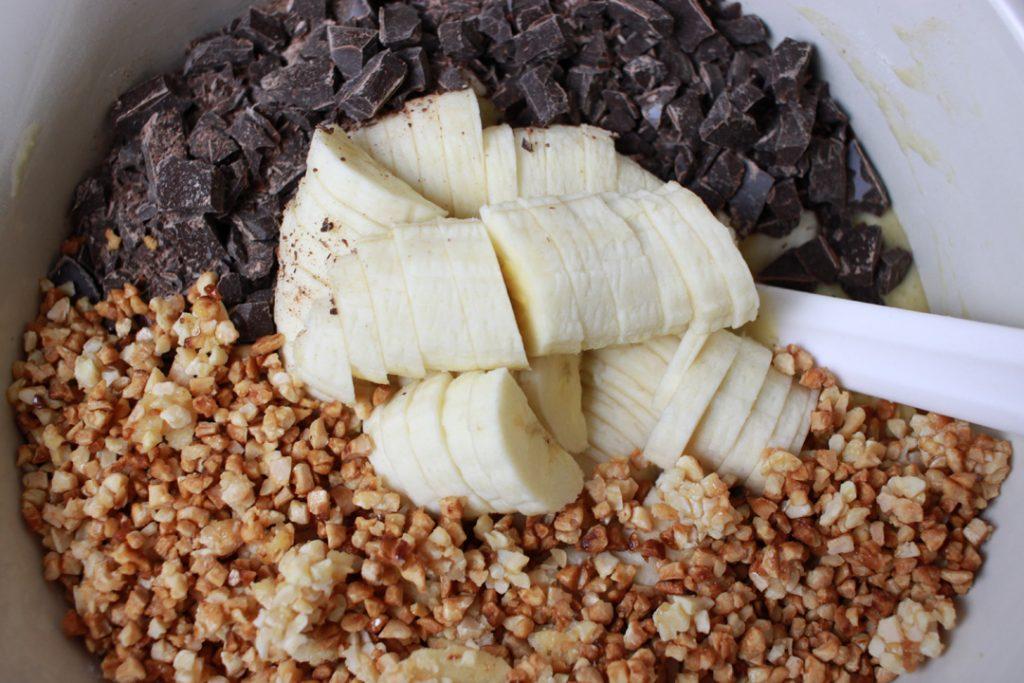 Bananen, Schokolade sowie kandierte Mandeln unter den Teig heben