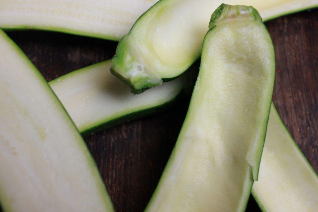 Die halbierten Zucchinis mit einem Löffel auskratzen