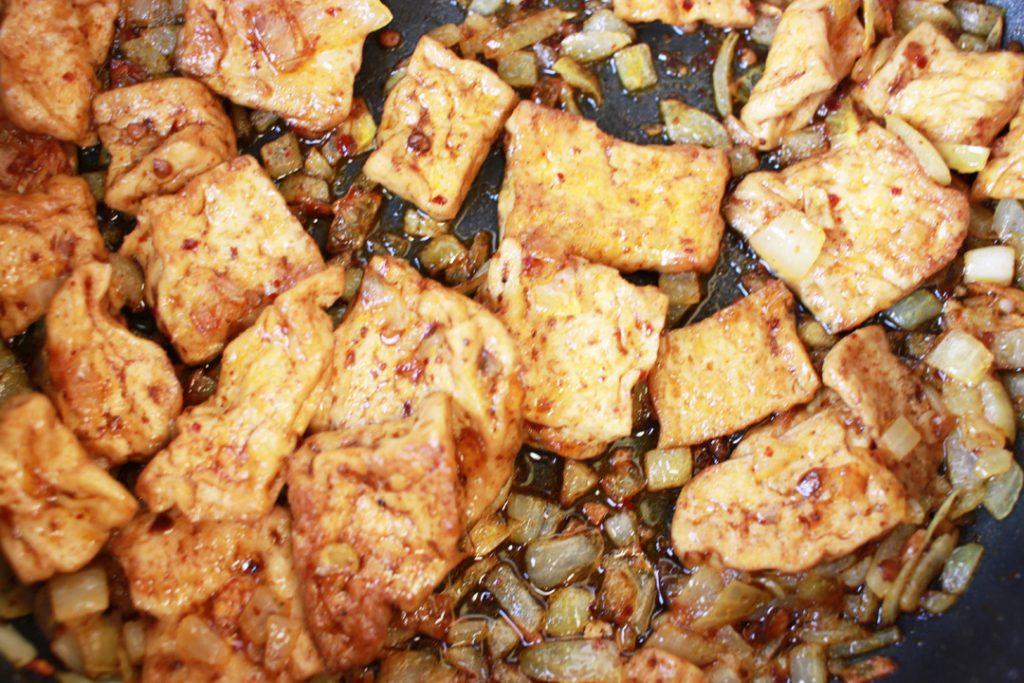 Für die vegane Hühnerbrühe den Szechuan Tofu mit den Zwiebeln anbraten