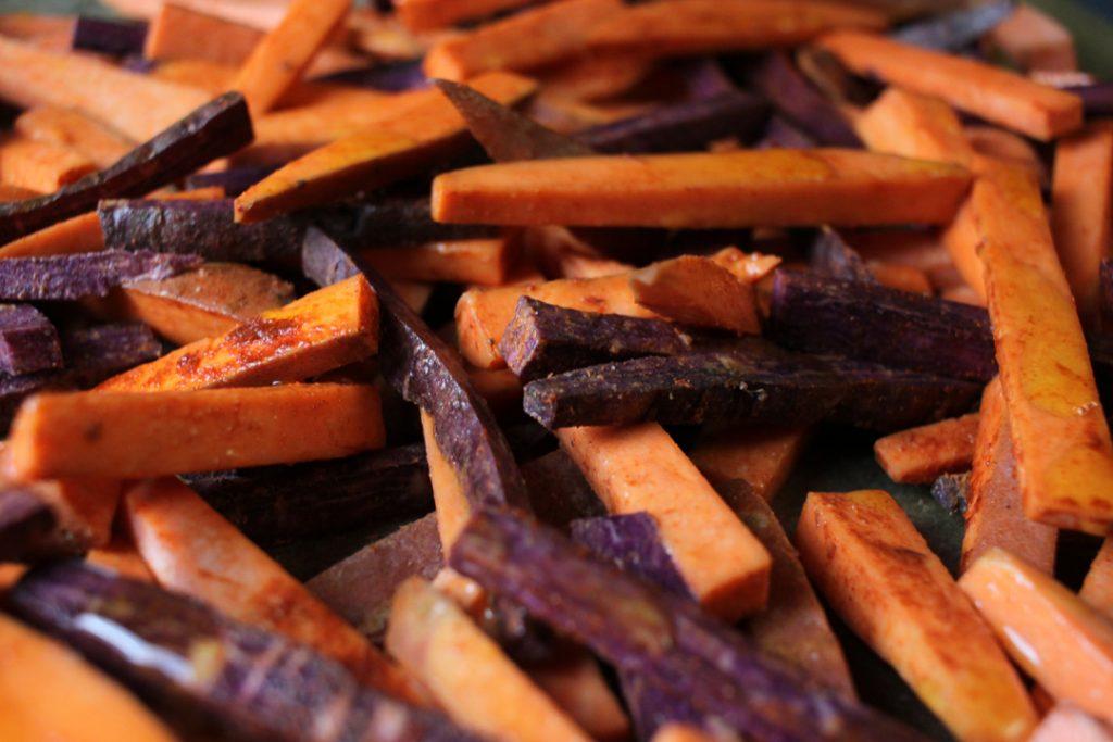 Die Süßkartoffel-Pommes mit Speisestärke, Salz und Paprika mischen