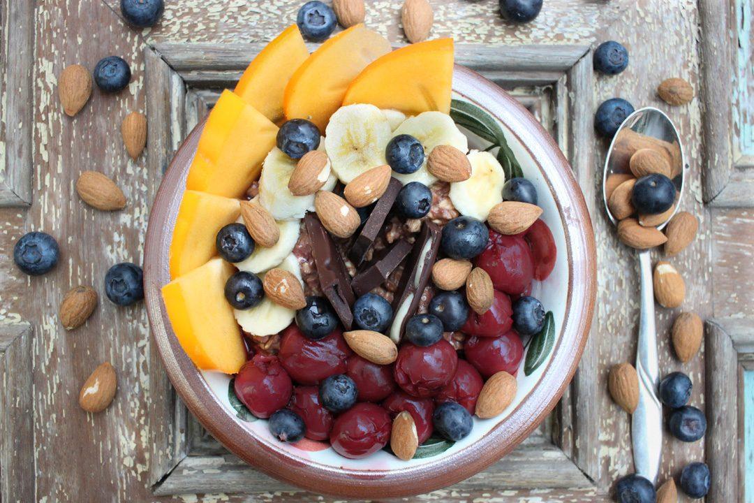 Schokoladen-Porridge mit heißen Kirschen , frischem Obst und Mandeln