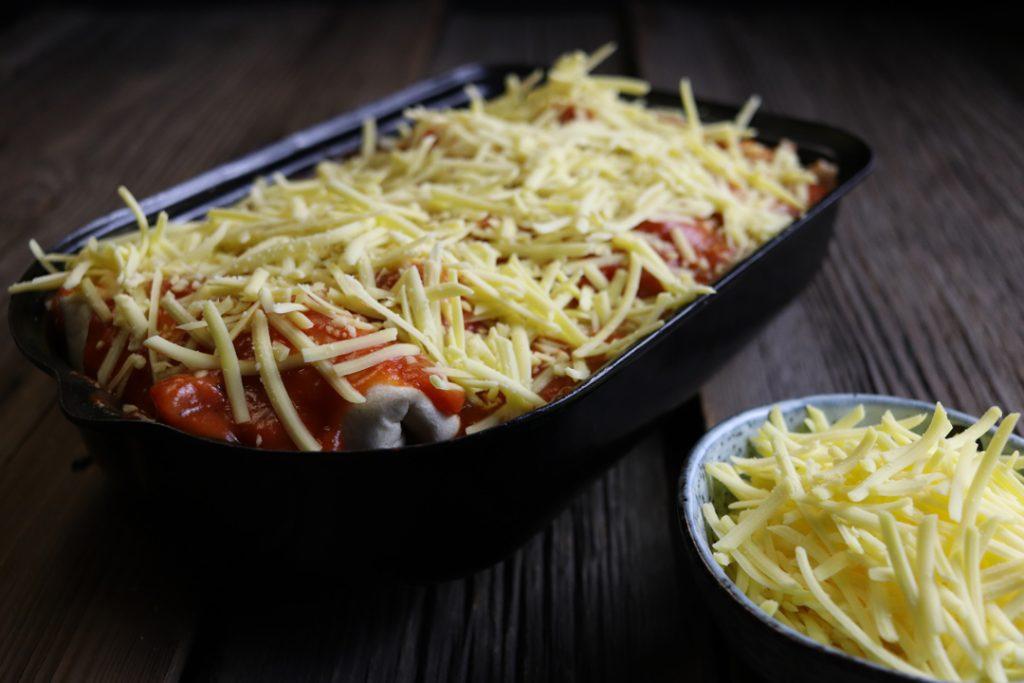 Vegane Enchiladas zusammen mit der übrigen Soße sowie dem restlichen veganen Streukäse im Ofen überbacken